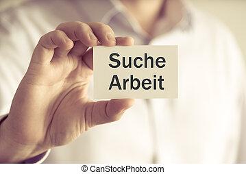 """Businessman holding message card """"SUCHE ARBEIT"""" written in..."""