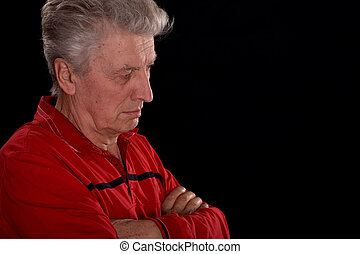 melancholy old man in red on a black background