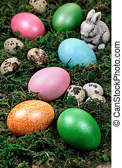 Easter colored eggs scattered on a green moss as an element...