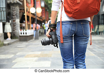 young woman tourist with camera on street in chengdu,china