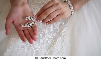 Bride holding earrings in hand