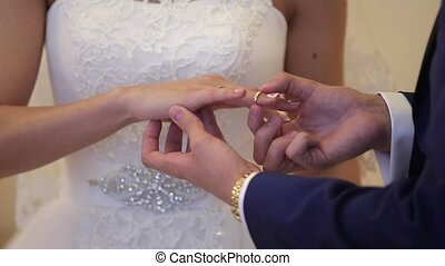 Groom puts on ring to bride hand on ceremony - Groom puts on...