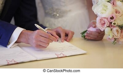 Groom signing document on wedding ceremony closeup