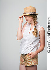 Smiling woman wearing summer straw fedora hat - Side view of...