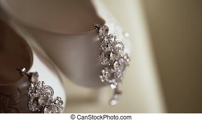 Beautiful earrings and white womens shoes closeup