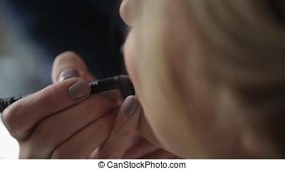 Makeup artist doing makeup for young blonde caucasian woman