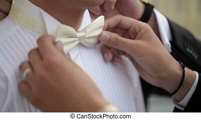 Friend fixing bowtie for the groom - Friend fixing white...