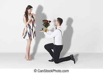 Young man surprising woman with engagement