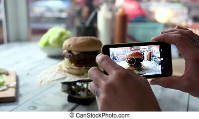 Cell phone photographing burger. Hamburger on table. Try...