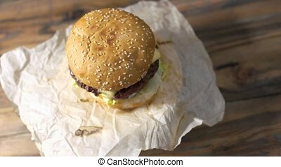 Burger on wooden background. Top view of fresh hamburger.