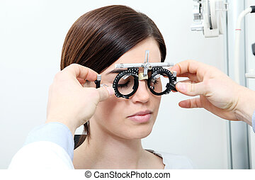 optician with trial frame, optometrist doctor examines eyesight of woman patient