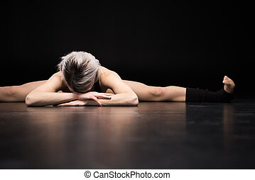 young woman dancer stretching on black - Sporty young woman...
