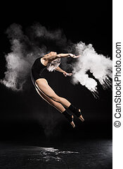 side view of woman in bodysuit with dust jumping