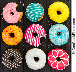 Different colorful donuts on black wooden background