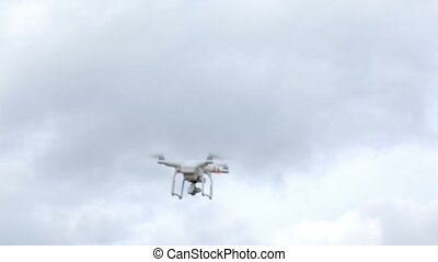 Quadcopter flying in the sky and landing at sunny day