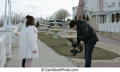 Cameraman with electronic gimbal steadicam in hands shooting...
