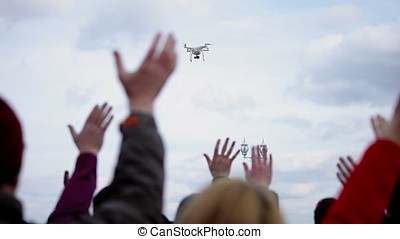 People waving for quadcopter flying in the sky