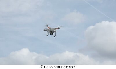 Quadcopter flying in the sky at sunny day