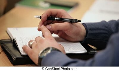 Man writing in notebook on lecture in class closeup