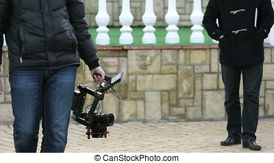 Cameraman with electronic gimbal steadicam in hands