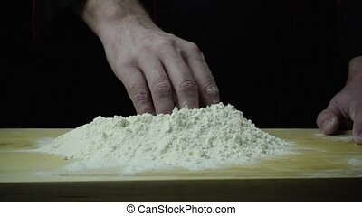 Chef hinders flour slow motion - Chef hand hinders the flour...