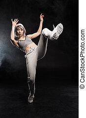 woman in sports clothing dancing on black