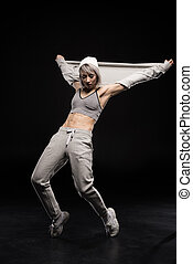 focused woman in sports clothing dancing on black