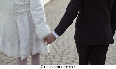Young lovely wedding couple walking on a street at winter