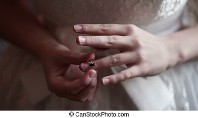 Bride put on ring on a finger closeup