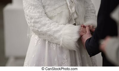 Bride and groom holding hands on ceremony at winter