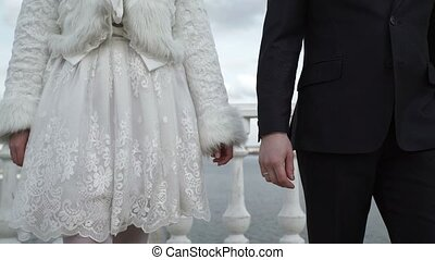 Young lovely wedding couple walking on a street and taking...