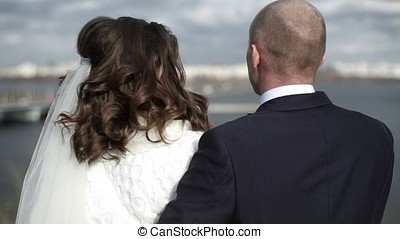 Young lovely wedding couple on embankment looking to the...