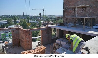 builder worker in safety protective equipment installing...