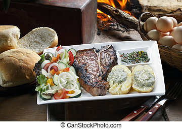 t-bone - t bone steak with potato salad and vegetables