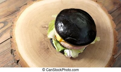 Black burger on wooden background. Meat and lettuce leaves....