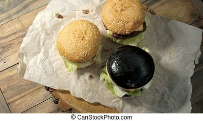 Three hamburgers on wooden background. Dark and light...