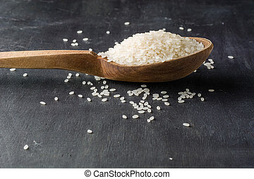 A handful of white polished rice in a wooden old spoon. Dark...