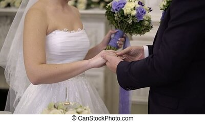 Groom puts on ring to bride's hand on ceremony - Groom puts...