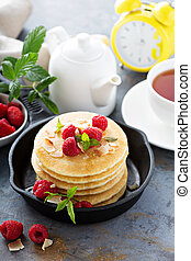 Stack of fluffy buttermilk pancakes with raspberry and...