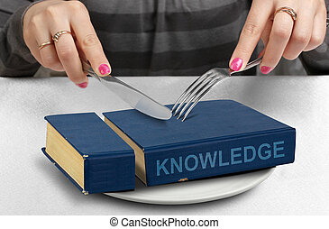 consume knowledge concept, hands cut book on plate - consume...