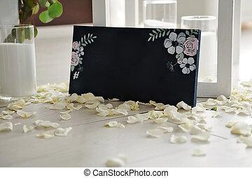 Hashtag written on blackboard with bouquet of flower