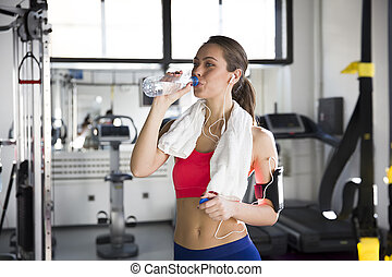 Portrait of a woman at the gym drinking water