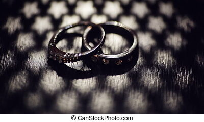 two wedding rings on a table with a shadow in the shape of...