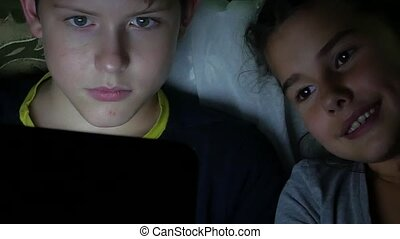boy teen and girl plays on the laptop at night online games...