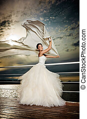 Fianceacute; in the wind - Pretty lady in a wedding dress on...