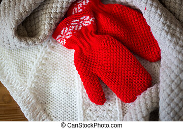 Winter baby clothes, scarf and mittens on wooden background
