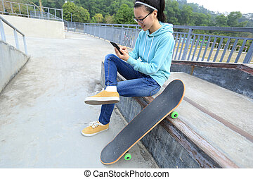 young skateboarder use cellphone  at skatepark