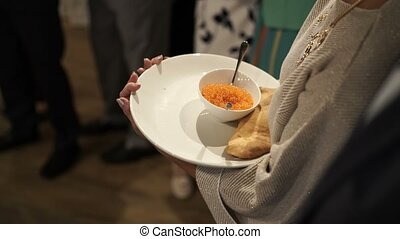 Red caviar and bread in woman's hands