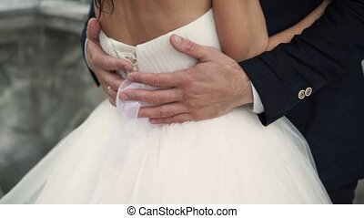 Wedding couple embracing at cloudy day