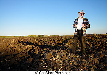 farmer in a field - An elderly farmer standing in a plowed...